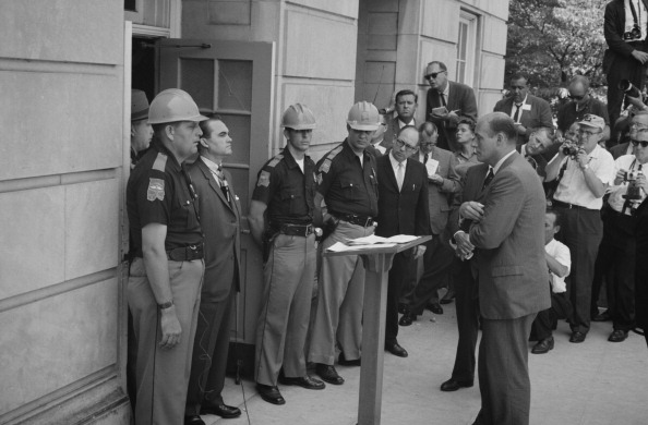 George Wallace (1919-1998) Governor of Alabama for four terms between 1963 and 1987. Wallace attempting to block integration at the University of Alabama, standing defiantly at a door while being confronted by US Deputy Attorney General Nicholas Katzenbac